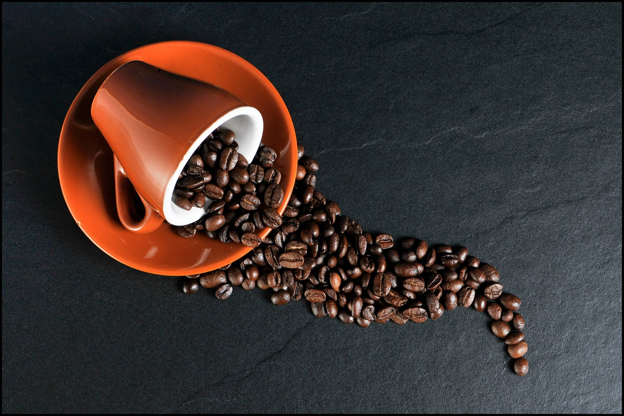 Coffee cup spilling coffee beans