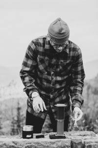 man standing near gray tumberls