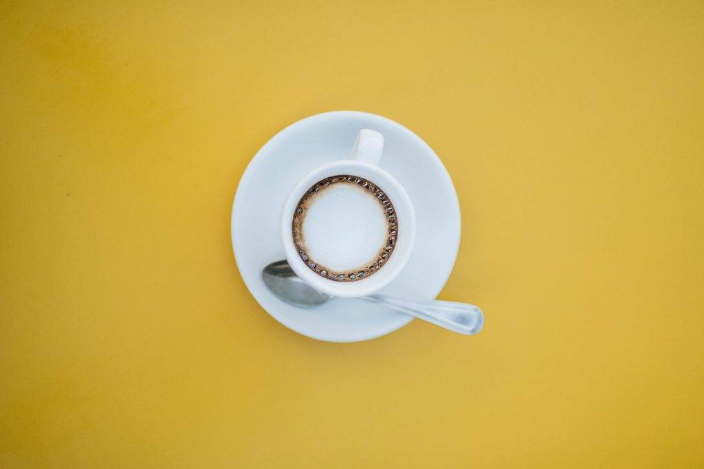 filled white teacup on saucer with teaspoon