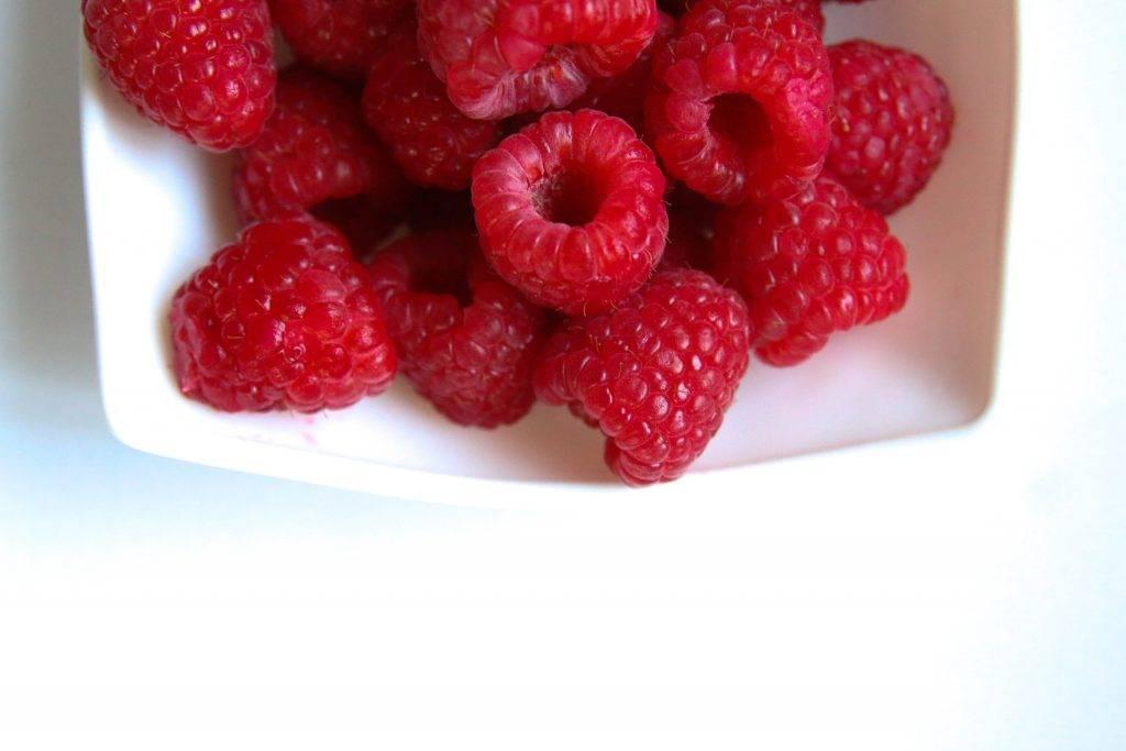 red raspberry on white ceramic plate