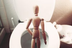 brown wooden mannequin on white ceramic toilet bowl