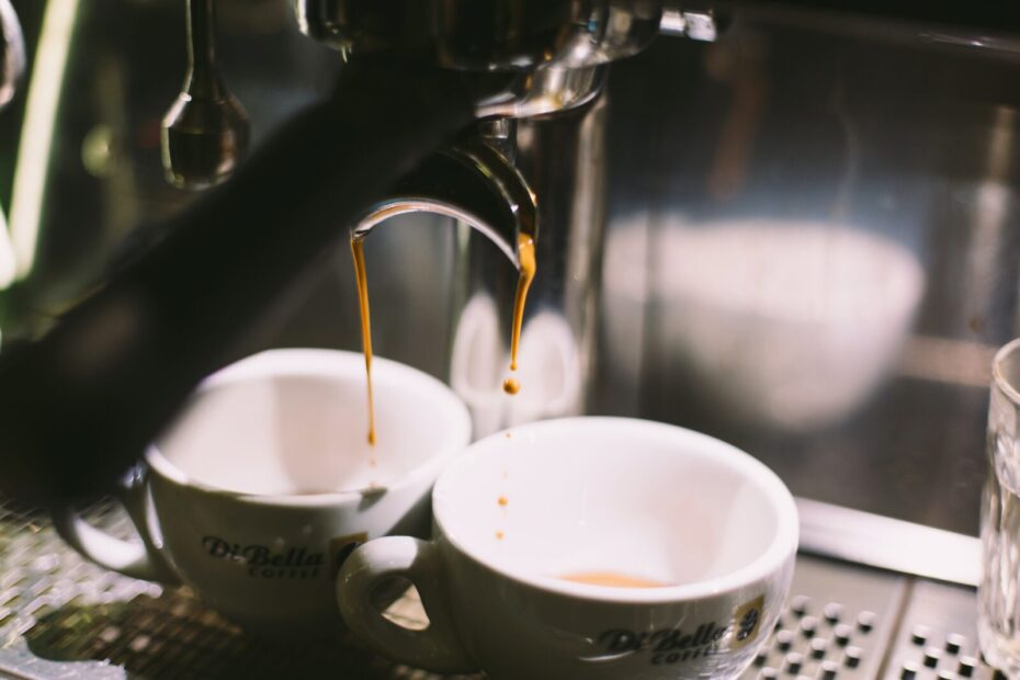 two white ceramic mugs on coffeemaker