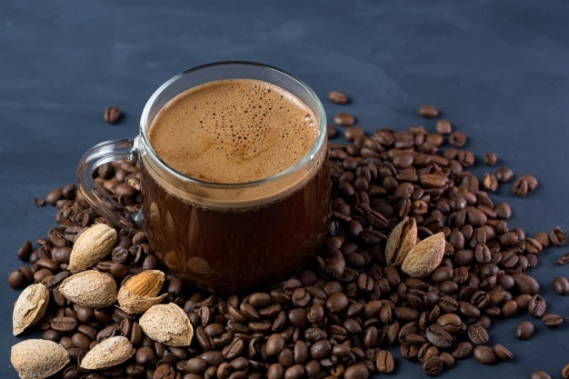 glass cup coffee with grated roasted almonds concrete table scattered roasted grains 97245 1254